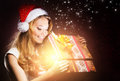 A young teenage girl opening the present happy and emotional magical christmas box Stock Images