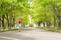 Young teenage girl riding a scooter along tree lined country road heading directly for the camera Royalty Free Stock Photos