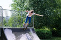 Young teenage girl roller blading active energetic launching herself from the top of a cement ramp in a skate park Royalty Free Stock Photography