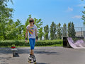 Young teenage girl roller skater beautiful in a skate park practising her steps on her rollerblades in the summer sunshine Royalty Free Stock Images