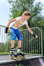 Young teenage girl roller skating balancing in her rollerblades at the top of a cement ramp in a skate park psyching herself to Stock Photos