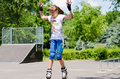 Young teenage girl in a skate park balancing on tips of her roller blades with her hands the air as she prepares to perform move Stock Image