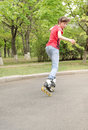 Young teenage girl skating on roller blades along rural tree lined road turning her head watch something her right she speeds Royalty Free Stock Image