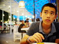 Young teenager a healthy asian thai boy with short hair black eyes yellow color wearing deep blue shirt sitting on a table in semi Royalty Free Stock Photos