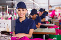 Young textile machinist beautiful using sewing machine in clothing factory Royalty Free Stock Image