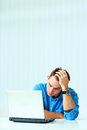 Young thoughtful businessman in blue shirt sitting at the table with laptop office Stock Images
