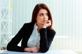 Young thoughtful businesswoman sitting on her workplace and looking away in office Royalty Free Stock Image
