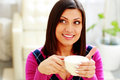 Young thoughtful happy woman holding cup of coffee and looking up Royalty Free Stock Photo