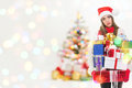Young tired woman in christmas euphoria with many presents caucasian brunette holding colorful wearing santa hat against blurred Stock Image