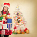 Young tired woman holding heavy christmas presents cute and exhausted caucasian brunette many standing next to tree Stock Image