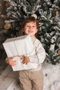 Young toddler Caucasian Boy Holding Christmas Present In Front Of Christmas Tree. Cute happy smiling boy. Vertical photo