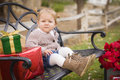 Young toddler child sitting on bench with christmas gifts outsid happy outside Royalty Free Stock Photography