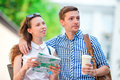 Young tourist couple traveling on holidays in Europe smiling happy. Caucasian family with city map in search of