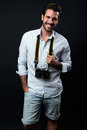 Young tourist man with vintage photo camera. Isolated on black. Royalty Free Stock Photo