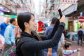 Young tourist woman taking selfie at street maket in hong kong outdoor Royalty Free Stock Photo