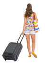 Young tourist woman wheel bag going straight rear view Stock Image