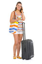 Young tourist woman with wheel bag talking mobile phone isolated on white Royalty Free Stock Images