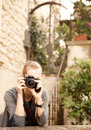 Young traveler blond woman holding camera Stock Images
