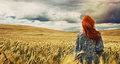 Young traveller standing back on plain field and breathtaking vi fashion red hair woman outdoor view of dramatic storm sky in the Royalty Free Stock Photos