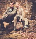 Young travellers happy smiling couple sitting on a rock Royalty Free Stock Photography