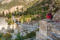 Young trekker preparing to cross suspension bridge annapurna region in nepal Royalty Free Stock Photos