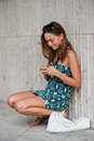 Young trendy girl browsing the internet with her cell phone student in urban environment Royalty Free Stock Photo