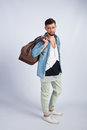 Young trendy guy in the studio is a travel bag Royalty Free Stock Photo
