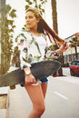 Young trendy long haired woman posing with her longboard enjoying good day in summer Royalty Free Stock Photo