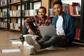 Young two african men students reading books using laptop Royalty Free Stock Photo
