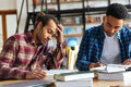 Young two men students sitting in library reading books Royalty Free Stock Photo