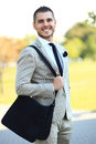 Young urban businessman running in street smiling wearing jacket and leather laptop bag on Royalty Free Stock Photography