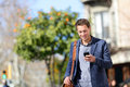 Young urban professional man using smart phone businessman holding mobile smartphone app texting sms message wearing jacket Royalty Free Stock Image
