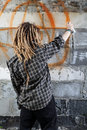 Young vandal drawing graffiti on the wall Royalty Free Stock Images