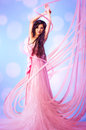 Young vietnamese woman with pink dress creating from thread Stock Image