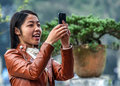 Young vietnamese woman takes a selfie hanoi vietnam march wearing leather vest picture with her smart phone Royalty Free Stock Photo