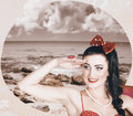 Young vintage styled female wearing retro swimwear looking out to sea Stock Images