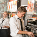 Young waiter and waitress working in bar serving coffee Royalty Free Stock Images