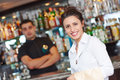 Young waitress at service in restaurant catering female cheerful worker with barman background Stock Image