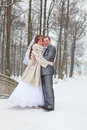 Young wedding couple embracing on snowy park Stock Photo