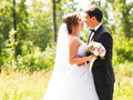 Young wedding couple enjoying romantic moments outside on a summer meadow Royalty Free Stock Photo