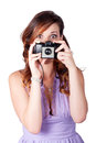 Young wide eyed caucasian woman taking picture with vintage camera over white background Royalty Free Stock Image