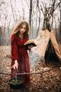 Joven bruja en otoño bosque