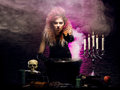 Young witch making witchcraft in a hallowen dungeon and beautiful halloween concept Royalty Free Stock Photo