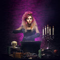 Young witch making witchcraft in a hallowen dungeon and beautiful halloween concept Royalty Free Stock Photography