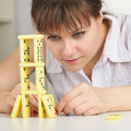 Young woman accurately builds tower of dominoes Stock Photography