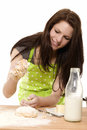 Young woman adding flour to dough Stock Photo