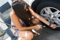 Young woman adds air to her car tire Royalty Free Stock Photos