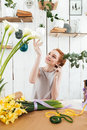 Young woman admire the beautiful flowers in workshop Royalty Free Stock Photo