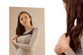 Young woman admiring herself in a mirror beautiful preening as she looks at her shapely body and stylish clothes Stock Photography