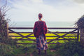Young woman admiring sea view by rural fence Royalty Free Stock Photo